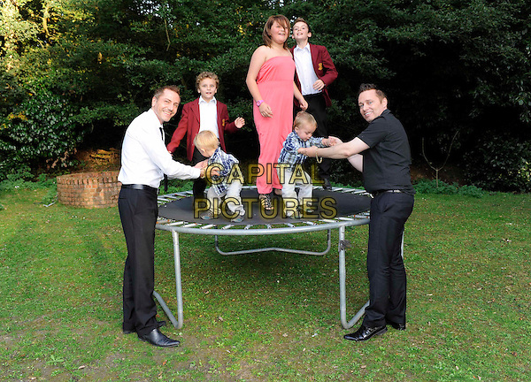 Tony And Barrie Drewitt-Barlow.(civil partners) with their children, twins Jasper And Dallas, Orlando, Aspen and  daughter Saffron, at home in Essex, England 24th September 2011.**EXCLUSIVE ALL-ROUNDER**.full length black shirt trampoline kids children family trousers .CAP/FIN.©Steve Finn/Capital Pictures........THIS IS A SPEC PICTURE>FEE REQUIRED FOR USEAGE.CAP/FIN.©Steve Finn/Capital Pictures.