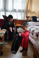Blind Tibetan Headmaster Nyima Wangdu of the School for the Blind In Tibet listens as his daughter Tenzin Dichen plays at home inside the campus in the capital city of Lhasa, September 2016.