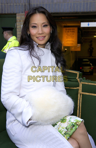 LUCY LIU .Opens the Harrods January Sale, Harrods, Knightsbridge, London, January 3rd 2005..half length sitting in carriage white coat fur muff.Ref: DH.www.capitalpictures.com.sales@capitalpictures.com.©David Hitchens/Capital Pictures .