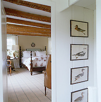 View of the bedroom with a reproduction Ball & Bell bed from the hallway with a set of 18th-century duck prints framed in black reproduction faux bamboo
