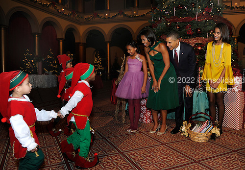 """United States President Barack Obama, first lady Michelle Obama (2nd,L) and daughters Malia (R) and Sasha greet children dressed as elves prior to attending performances at the annual """"Christmas in Washington"""" gala, December 11, 2011, Washington, DC.   .Credit: Mike Theiler / Pool via CNP"""
