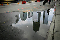 Tenth anniversary of 9/11.  Rebuilding at the World Trade Center site.  The view from Greenwich Street north to Ground Zero.  L to R: reflected in puddle, World Financial Center buildings, Goldman Sachs, under-construction 1 WTC and 7 WTC  Photo by Ari Mintz.  8/7/2011.