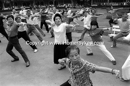 The Peoples Republic of China. Shanghai. 2000.  Around 6am each morning Fuxing Park begins to fill up. To the sounds of numerous cassette players, groups perform ballroom dancing, fan dances, t?ai chi and free-style exercises with great seriousness.  This is continuing the traditions of communist collective activities.  Exercises over, people walk around chatting and laughing which makes exercise very much a social activity..
