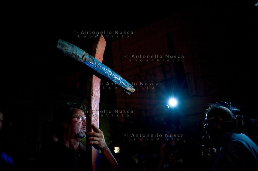La croce di legno ricavata utilizzando il legno delle barche utilizzate dai clandestini viene mostrata durante la fiaccolata per commemorare le vittime del naufragio. People attend the torchlight procession in memory of victims of the immigrant boat disaster in Lampedusa, Italy.
