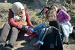 A refugee mother helps her daughter put on dry shoes on a beach near Molyvos, on the Greek island of Lesbos, on October 29, 2015, after they crossed the Aegean Sea from Turkey in a small overcrowded boat provided by Turkish traffickers to whom the refugees paid huge sums. They were received in Greece by local and international volunteers, then proceeded on their way toward western Europe.