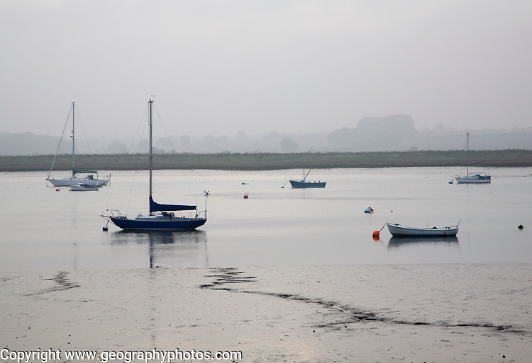 Boats at moorings on calm misty day on the River Deben, Ramsholt, Suffolk, England