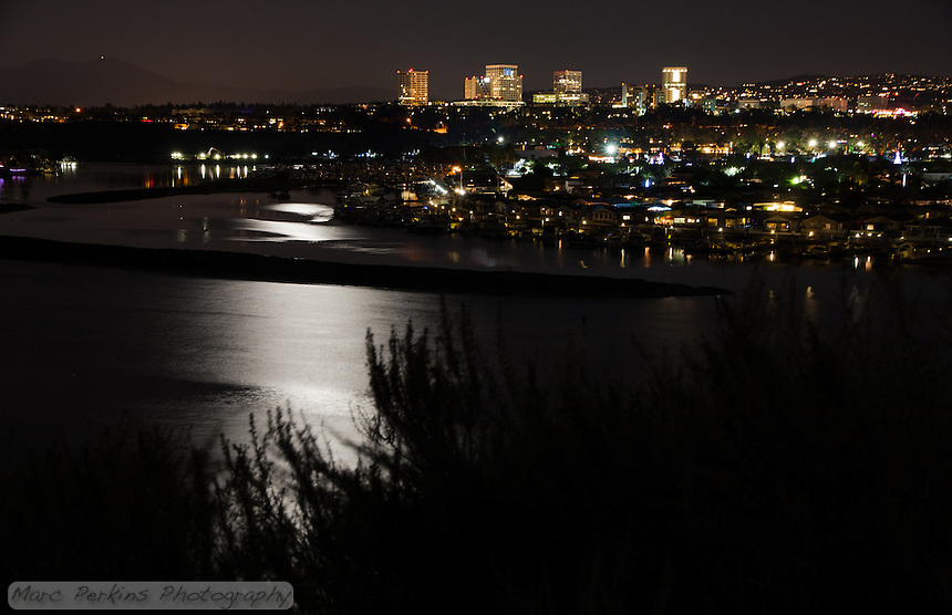 Moonlight reflects off the water of Lower Newport Bay (and partially Upper Newport Bay) with Newport Center's many tall buildings that surround Fashion Island in Newport Beach, CA.  Saddleback Mountain (Santiago Peak and Modjeska Peak) can be seen off in the distance, to the left.  This image is a minimally manipulated single-frame, long-exposure capture.