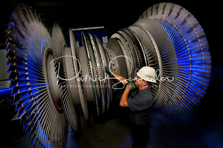 An employee of Siemens Charlotte Turbine-Generator Center inspects sections of a generator rotor system. Siemens state-of-the-art generator manufacturing operations include new-unit generator manufacturing as well as service repairs for steam turbines and generators. The Charlotte NC manufacturing facility was founded in 1967 by Westinghouse Electric Corporation to manufacture nuclear low pressure turbines. Siemens Charlotte plant is the primary service center for generator and steam turbine equipment in the Americas, and the lead plant for manufacturing new electrical generators. Internationally, Siemens AG is Europe's largest engineering conglomerate.