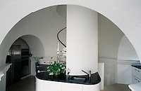The granite-topped units of this contemporary kitchen are set into the arches of the tower or oriented around the central staircase