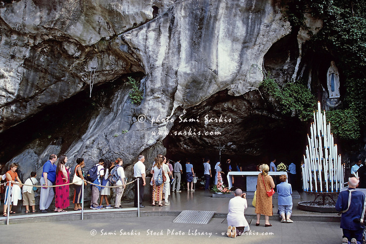Pilgrims visiting the Our Lady of Lourdes statue in the cave at Massabielle, Lourdes, France.