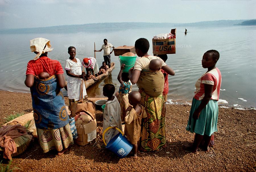 1994. Burundi. Lake Cyohoha. During the Rwandan Genocide, after crossing the lake on pirogues, Burundian Hutu refugees return to Ceru. Burundi. Lac Cyohoha. Pendant le génocide au Rwanda, après avoir traversé le lac en pirogue, des réfugiés hutus burundais retournent à Ceru.