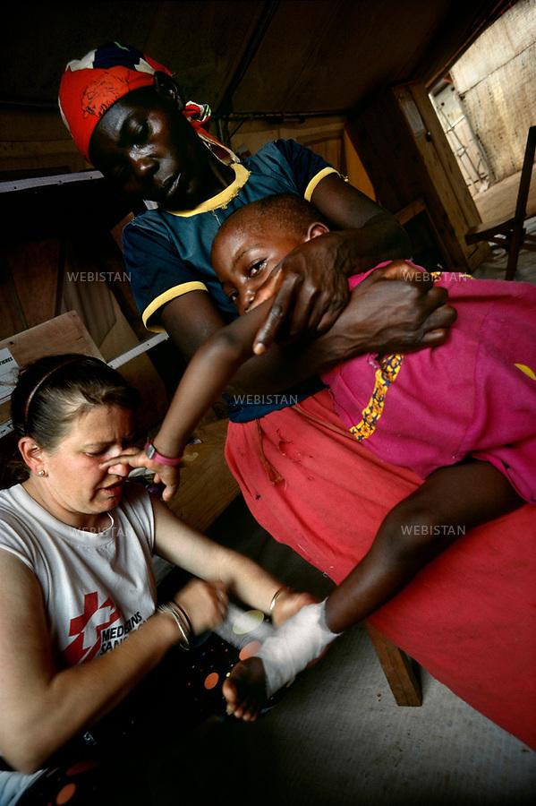 1994. Rwanda. Lake Cyohoha. Burengue Camp. During the Rwandan Genocide, a female doctor from Médecins Sans Frontières (MSF) takes care of the foot of a Hutu Burundian refugee girl. Rwanda. Lac Cyohoha. Camp de Burengue. Pendant le génocide au Rwanda, une femme médecin de Médecins Sans Frontières (MSF) soigne le pied d'une fillette réfugiée hutu burundaise.