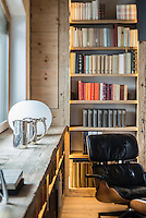 Detail of an Eames lounge chair in front of bespoke wall-to-wall wooden bookshelves