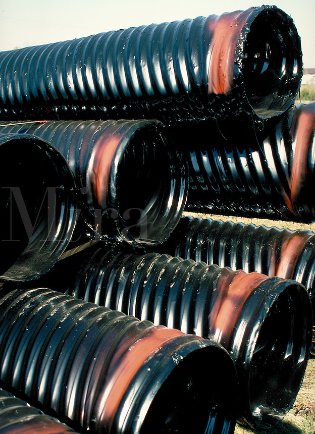 Pile of black plastic drainage pipe, vert. Hartford CT USA.