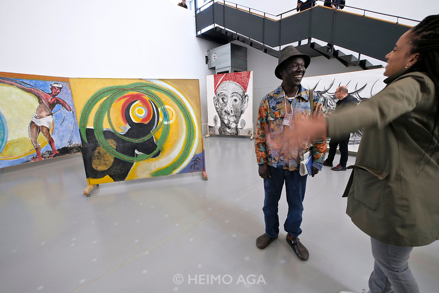 Kassel, Germany. Opening days of documenta14.<br /> documenta-Halle.<br /> El Hadji Sy (Senegal) with some of his paintings.