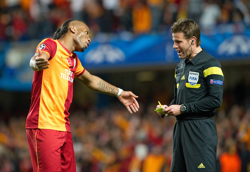 Galatasaray's Didier Drogba is shown a yellow card by Referee Felix Brych <br /> <br /> Photo by Ashley Western/CameraSport<br /> <br /> Football - UEFA Champions League First Knockout Round 2nd Leg - Chelsea v Galatasaray - Tuesday 18th March 2014 - Stamford Bridge - London<br />  <br /> &copy; CameraSport - 43 Linden Ave. Countesthorpe. Leicester. England. LE8 5PG - Tel: +44 (0) 116 277 4147 - admin@camerasport.com - www.camerasport.com