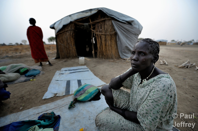 A displaced woman awakes in the morning after sleeping outside on the ground in front of rustic shelter in Agok, a town in the contested Abyei region where tens of thousands of people fled in 2011 after an attack by soldiers and militias from the northern Republic of Sudan on most parts of Abyei. Although the 2005 Comprehensive Peace Agreement called for residents of Abyei--which sits on the border between Sudan and South Sudan--to hold a referendum on whether they wanted to align with the north or the newly independent South Sudan, the government in Khartoum and northern-backed Misseriya nomads, excluded from voting as they only live part of the year in Abyei, blocked the vote and attacked the majority Dinka Ngok population. The African Union has proposed a new peace plan, including a referendum to be held in October 2013, but it has been rejected by the Misseriya and Khartoum. The Catholic parish of Abyei, with support from Caritas South Sudan and other international church partners, has maintained its pastoral presence among the displaced and assisted them with food, shelter, and other relief supplies.