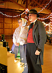 Old Bethpage, New York, USA. Decemer 26, 2014. Wife SHERRI GUTHRIE and husband CHART GUTHRIE, dressed in traditional 19th Century clothing, visit the Salce imported Italian olive oil booth inside the Barn, at night, on the historic, rustic grounds of Old Bethpage Village Restoration, transformed by candlelight and Christmas decorations into a Nineteenth Century holiday experience for Long Island visitors. Candlelight Evenings are held until December 30th.