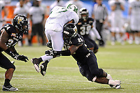 20 December 2011:  FIU linebacker Jordan Hunt (25) tackles Marshall running back Travon Van (7) in the second quarter as the Marshall University Thundering Herd defeated the FIU Golden Panthers, 20-10, to win the Beef 'O'Brady's St. Petersburg Bowl at Tropicana Field in St. Petersburg, Florida.