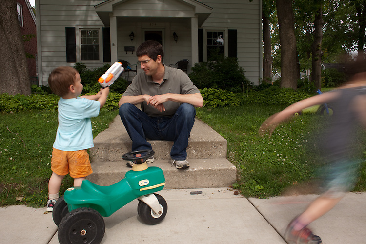 My husband bought our boys squirt guns because he thought they would have fun, and he got ones he thought would be big enough that they wouldn't be outgunned by other kids. The one-year-old aims at his dad, while the almost five-year-old runs away.