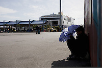 Pictured: A boy takes shelter from the sun with an umbrella Monday 07 March 2016<br /> Re: Migrants have been gathering at the port of Piraeus, near Athens, Greece.