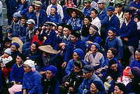 A CROWD of ethnic BAI PEOPLE watches a CHINESE OPERA PERFORMANCE in the farming town of DALI - YUNNAN, CHINA.