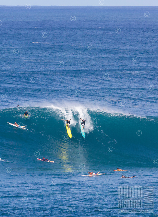 Surfers drop into a huge winter wave at Waimea Bay, North Shore, O'ahu.