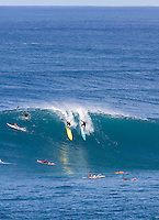 Surfers drop into a huge winter wave at Waimea Bay, North Shore, O'ahu.