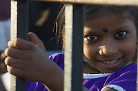 The faces of Mumbai, India, central Mumbai, a young girls child looking from the railinks at the road
