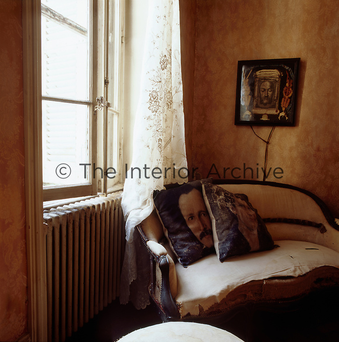 Two cushions are set on an antique sofa with a torn seat, which is placed in the corner of a room.