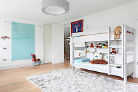 A white wood bunk bed in a childrens bedroom.