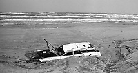 A partially buried junk car deposited on the beach by a noreaster storm , Daytona Beach, FL, December, 1984. (Photo by Brian Cleary/www.bcpix.com)