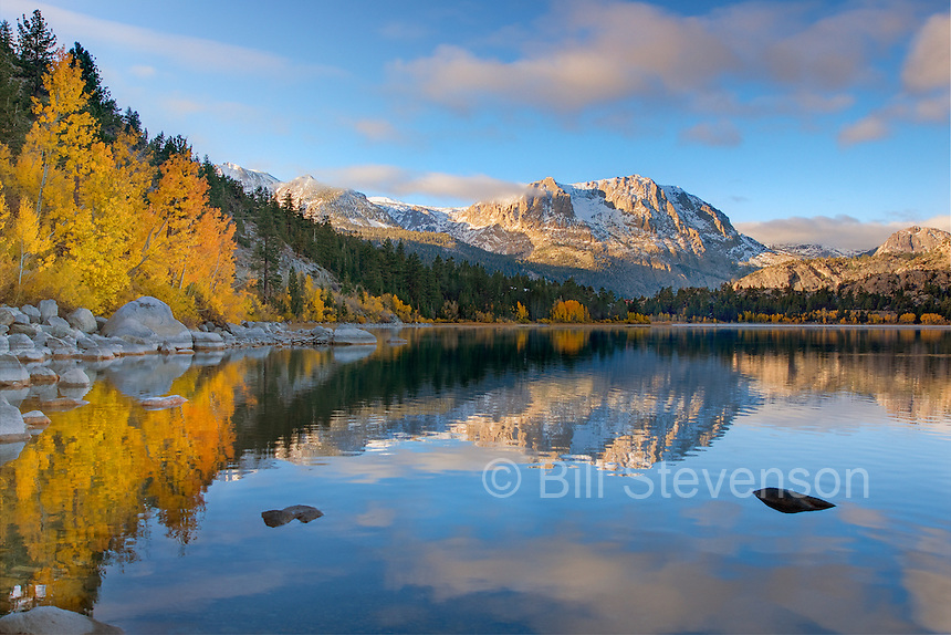 Yellow aspens clouds and a mountain  reflecting in June Lake in the Sierra mountains of California