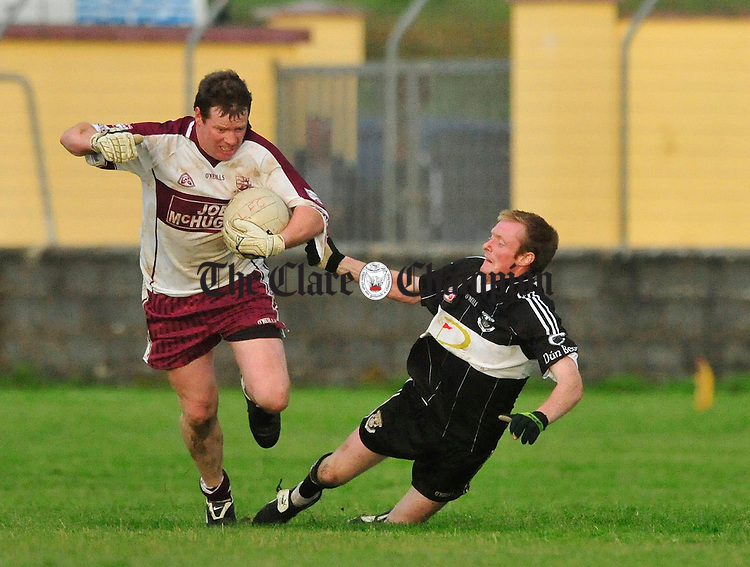 Aln Flaherty of Liscannor brushes off the tackle of Doonbeg's Enda Doyle. Photograph by Declan Monaghan