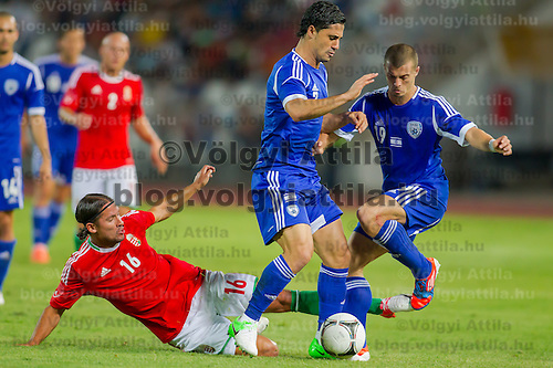 Hungary's Peter Halmosi (L) fights for the ball against Israel's Beram Kayal (C) and Israel's Elad Gabay (R) during a friendly football match Hungary playing against Israel in Budapest, Hungary on August 15, 2012. ATTILA VOLGYI