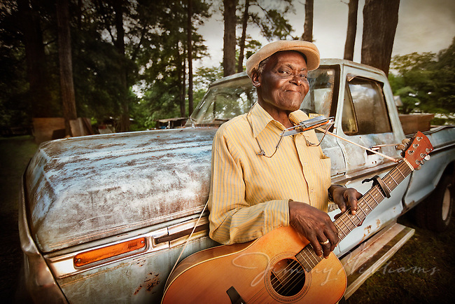 A blues musician leans again his old worn-out truck with his guitar and harmonica.