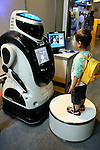 A young visitor looks at Sohgo Security Services (ALSOK)'s security robot Reborg-Q at Robo Japan 2008 in Yokohama, Japan on Saturday 09 October 2008. The robot is fitted with a face-recognition device.