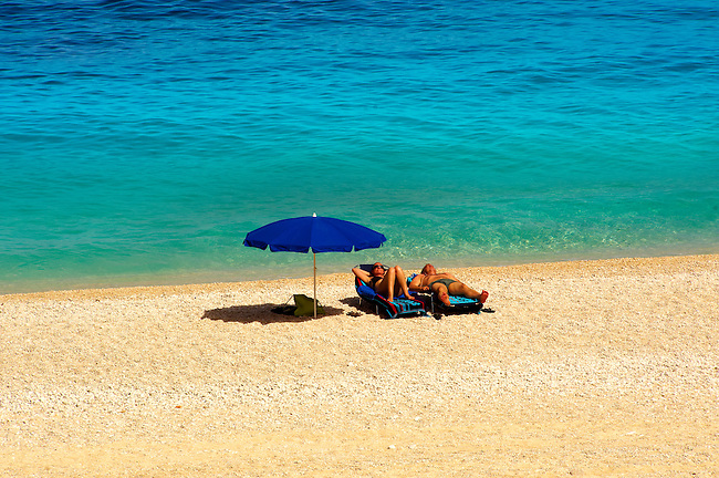 Couple sunbathing on the famous Turquoise waters of Myrtos Beach (??????? ??????), Kefalonia, Greek Ionian Islands