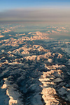 Aerial view over snow-covered mountains of the Sierra Nevada in winter with Lake Tahoe in the distance, California