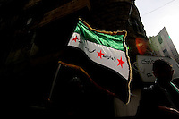 Photographer: Rick Findler/Borderline News..18.01.13 A Free Syrian flag catches the sunlight at a anti-Assad rally after Friday prayers, in the heart of Aleppo today, Northern Syria.