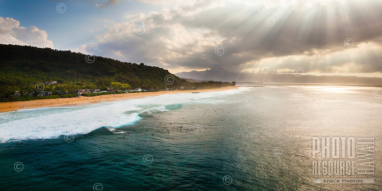 Surfers at Pipeline wait for a set to roll in while sun rays bathe the North Shore of O'ahu.