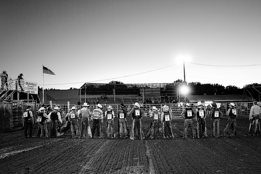 "Bull riders are introduced to a small crowd at Kicker's Korner, south of San Antonio, Texas on October 20, 2007.  Amateur bull riders across Texas compete in small town rodeos where their sport is often the highlight of the night.  Bull riders risk life and limb for rewards of around $1,000 for the winner, and they often claim to have riding ""in their blood."""