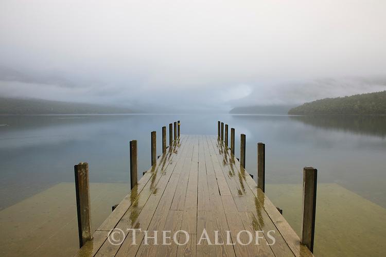 Wooden pier at Lake Rotoiti in rain; dawn; New Zealand, South Island