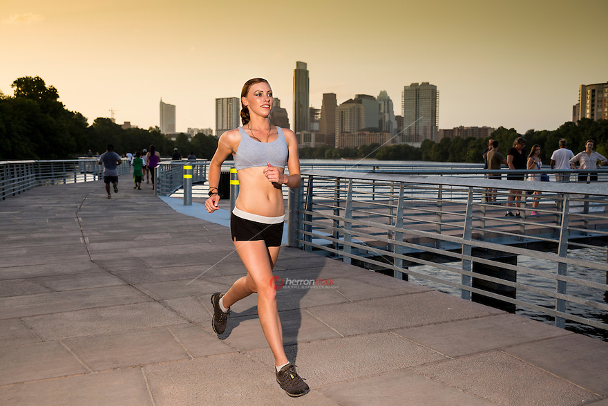 Athletic woman running jogging outside on the the Boardwalk Trail along Lady Bird Lake in downtown Austin as the ever growing Austin, Texas Skyline stands behind.