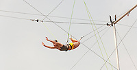 Students swing from a trapeze at the New York Trapeze School on a seasonably warm Sunday, July 5, 2015 in Coney Island in Brooklyn in New York over the 4th of July weekend. Some of the characters have moved from Times Square to Coney Island because of the increased competition.  (© Richard B. Levine)