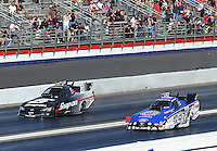 Feb. 17, 2013; Pomona, CA, USA; NHRA funny car driver Robert Hight (right) races alongside Cruz Pedregon during first round of eliminations at the Winternationals at Auto Club Raceway at Pomona. Mandatory Credit: Mark J. Rebilas-