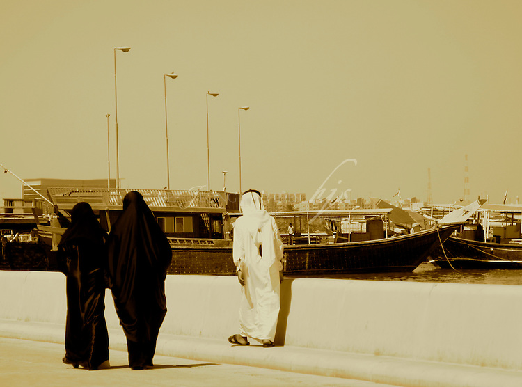Local Qatari ladies in their abaya and a man in his thobe walking along the corniche, Doha, Qatar | Sept 09