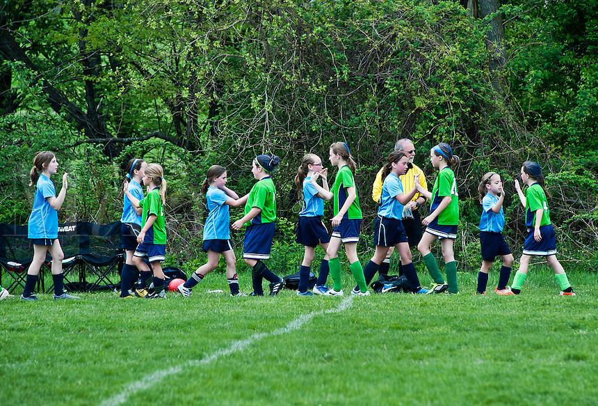 Youth girls post soccer game team handshake,