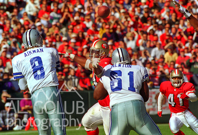 San Francisco 49ers vs. Dallas Cowboys at Candlestick Park Sunday, November 13, 1994.  49ers beat Cowboys 21-14.  Dallas Cowboys quarterback Troy Aikman (8) passes over San Francisco 49ers defensive tackle Dana Stubblefield (94).  (