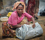 A Rohingya woman, having just crossed the border from Myanmar, rolls up a tarp as she waits to complete registration in the Kutupalong Refugee Camp near Cox's Bazar, Bangladesh. More than 600,000 Rohingya have fled government-sanctioned violence in Myanmar for safety in Bangladesh.